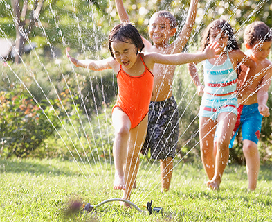 children-running-through-water-sprinkler-393